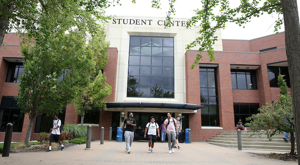three students walk in front of the JCCC student center